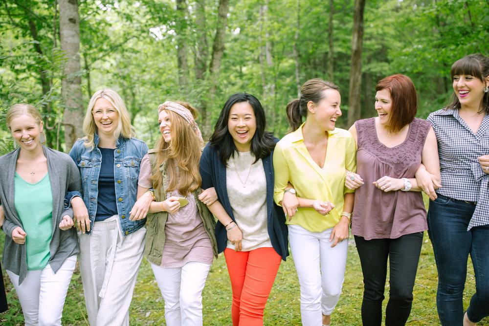 6 women walking arm in arm